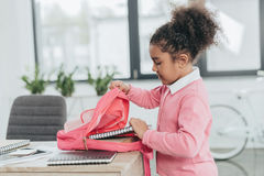 Cute little girl looking in pink backpack while standing at table in office Stock Photography