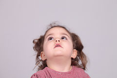 Cute little girl looking up. Against of white background.Studio shot. Isolated Royalty Free Stock Photography