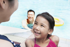 Cute little girl looking up at her mother by the pool Stock Photography