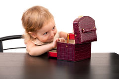 Cute little girl looks in a casket Royalty Free Stock Images