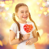 Cute little girl in love with candy lollipop heart. Valentine`s day. Royalty Free Stock Images