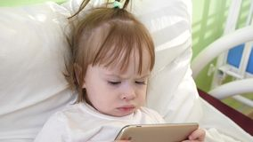Cute little girl is lying on bed in children`s hospital, watching funny cartoons on the smartphone. Cute little girl is lying on bed in children`s hospital royalty free stock photos