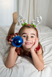 Cute Little Girl lying on bed with christmas bubble Royalty Free Stock Photo