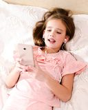 Cute little girl lying on the bed listening to music and singing. Using smartphone and listening on headphones earphones royalty free stock image