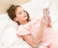 Cute little girl lying on the bed and listening to music using s royalty free stock images