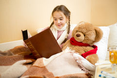 Cute little girl lying in bed and reading book to teddy bear Royalty Free Stock Image