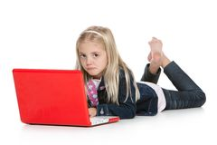 Cute little girl lying down with laptop isolated o Royalty Free Stock Image
