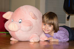 Cute little girl lying on the floor with her stuffed toy pig stock image