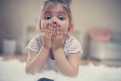 Cute little girl lying on floor. Shocked little girl watching something on TV Stock Image