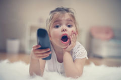 Cute little girl lying on floor. Shocked little girl watching TV lying on floor with remote control in hand Stock Photo