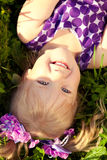Cute little girl lying on the grass in the park. Smiling nice ch Royalty Free Stock Images