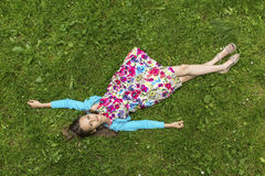 Cute little girl lying on green grass Royalty Free Stock Photos