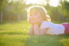 Cute little girl lying in green grass Stock Images