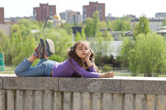 Cute little girl lying on a high stone parapet and dreaming with closed eyes over city background Royalty Free Stock Image