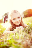 Cute little girl lying on the meadow. In summer day stock photo