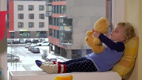 Cute little girl lying on radiator by window with a teddy bear. winter snow fall stock video footage