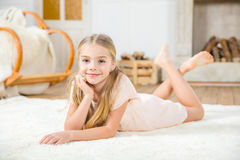Cute little girl. Lying on white carpet and smiling at camera Stock Image
