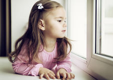 Cute little girl lying on the windowsill Royalty Free Stock Image