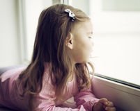 Cute little girl lying on the windowsill Royalty Free Stock Images