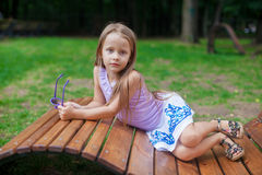 Cute little girl lying on wooden chair and Stock Image