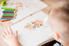 Cute little girl make applique glues colorful house, applying color paper using glue while doing arts and crafts in preschool or h royalty free stock image
