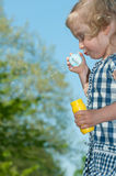 Cute little girl makes soap bubbles Royalty Free Stock Photos