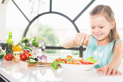 Cute little girl making salad. Child cooking. Healthy food Royalty Free Stock Images