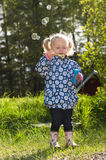 Cute little girl making soap bubbles in spring Stock Photography