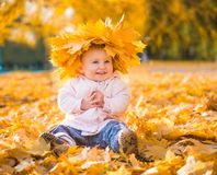 Cute little girl among maple leaves Stock Photos