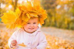 Cute little girl among maple leaves Royalty Free Stock Photography