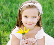 Cute little girl on the meadow with flower Stock Photo