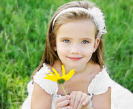 Cute little girl on the meadow with flower Royalty Free Stock Photography