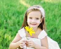 Cute little girl on the meadow with flower Royalty Free Stock Photo