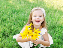 Cute little girl on the meadow with flower in summer day Stock Images