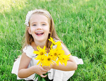 Cute little girl on the meadow with flower in summer day Royalty Free Stock Photos