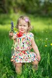 Cute little girl in a meadow full of flowers Royalty Free Stock Photos