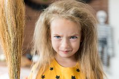 Cute little girl with messy hair, holding a broom and dressed up as a witch standing in Halloween decorated living room. stock photos