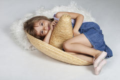 Cute little girl in a mexican big hat, sumbrero. Full length portrait of a little girl sitting in fetal position in a big mexican hat, sumbrero, studio image Stock Photos