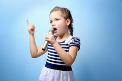 Cute little girl with microphone. On color background royalty free stock photography