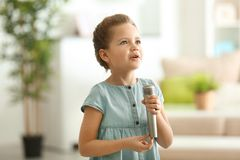 Cute little girl with microphone at home royalty free stock photos