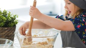 Cute little girl mixing the dough for cookies with wooden spoon in glass bowl. Horizontal royalty free stock photo