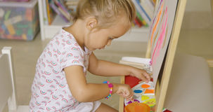 Cute little girl mixing paints for her painting Stock Image