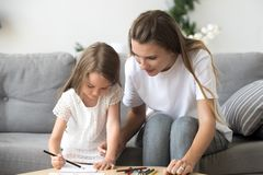 Cute little girl with mom drawing with colored pencils together stock image