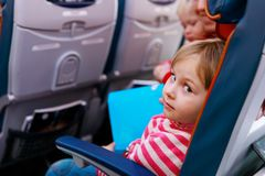 Cute little girl with mom and sister travel by plane, family in flight. Cute little girl with mom and sister travel by plane, family with kids in flight royalty free stock photography