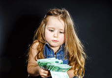 Cute little girl with money euro in her hand. Royalty Free Stock Images