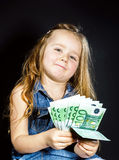 Cute little girl with money euro in her hand. Royalty Free Stock Photos