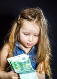 Cute little girl with money euro in her hand. Stock Photo