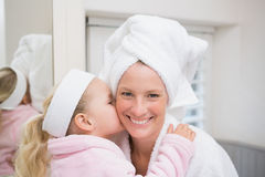 Cute little girl with mother in bathrobes Stock Image