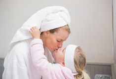 Cute little girl with mother in bathrobes Stock Photos
