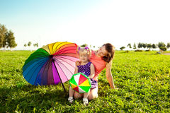 Cute little girl with mother colored balloons and rainbow umbrel Stock Photography